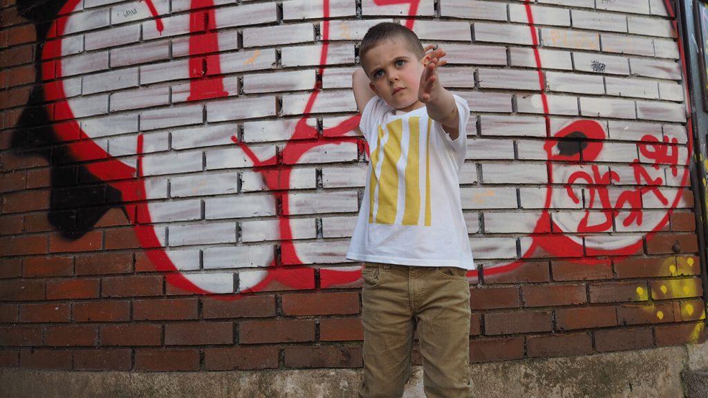 Снимка на дете на фона на графит, облечено в бяла тениска - История за драсканици и петна от боя