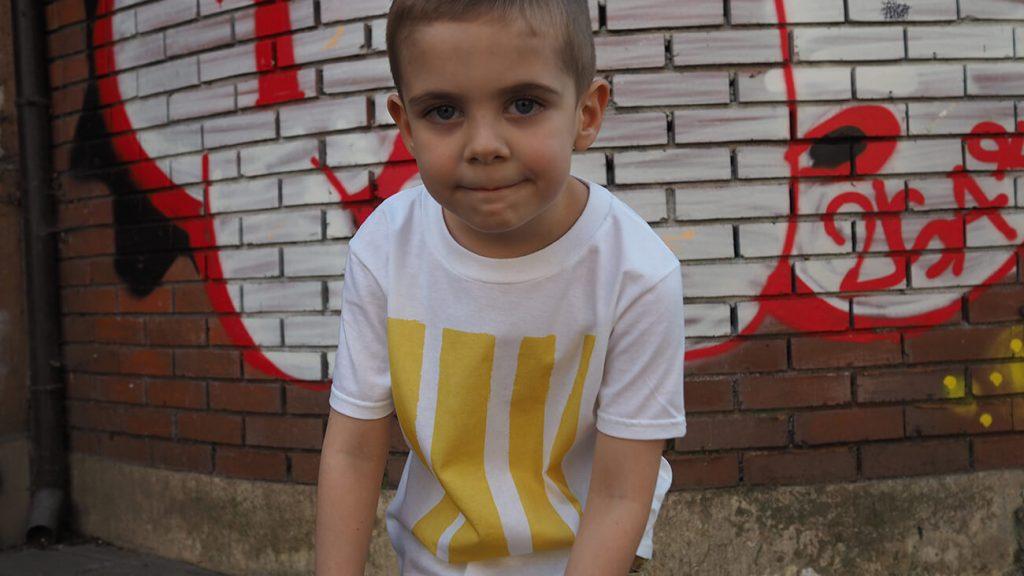 Снимка на дете на фона на графит, облечено в бяла тениска - История за драсканици и петна от боя-2