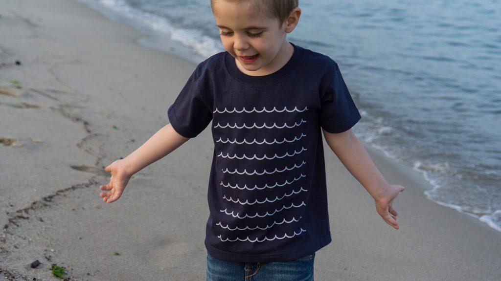 """Снимка на дете на плажа, което е облечено в синя тениска от колекцията """"Обичаме Морето"""""""