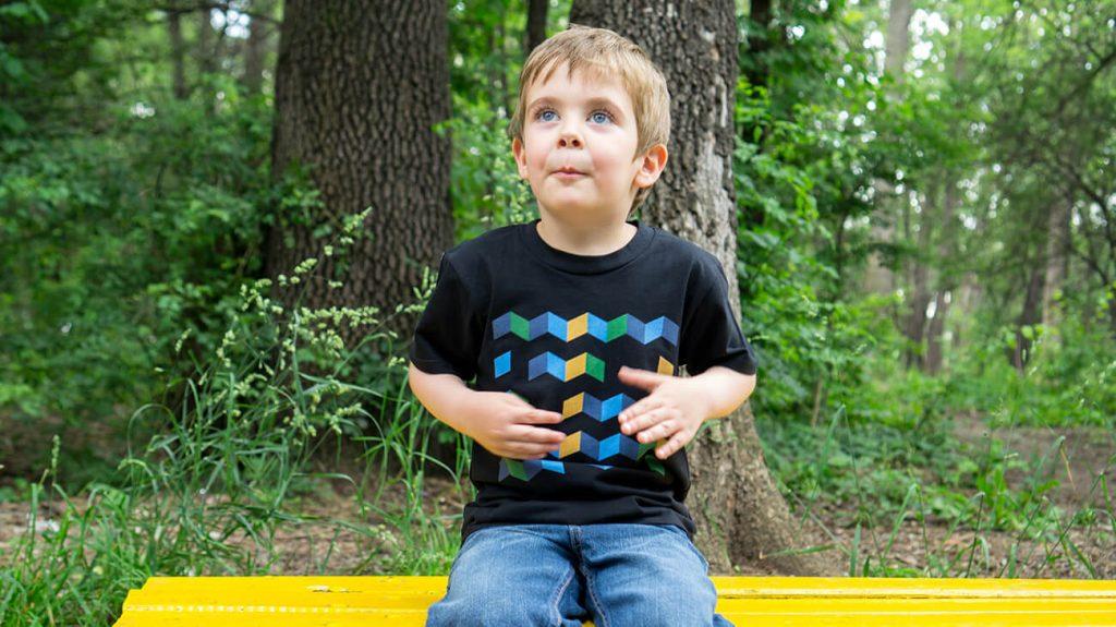 """Момчене на пейка, което е облечено в черна тениска от лятната колекция """"Обичаме Морето"""""""