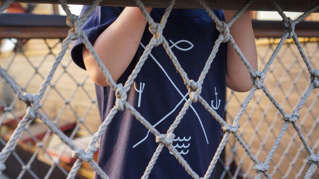 """Момченце на детска площадка, облечено в синя тениска от колекията """"Обичаме Морето"""""""