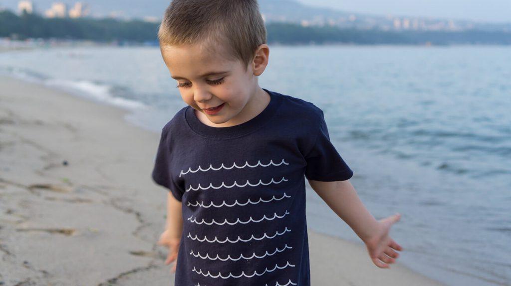 """Дете на плажа, облечено в синя тениска от лятната колекция """"Обичаме морето"""""""