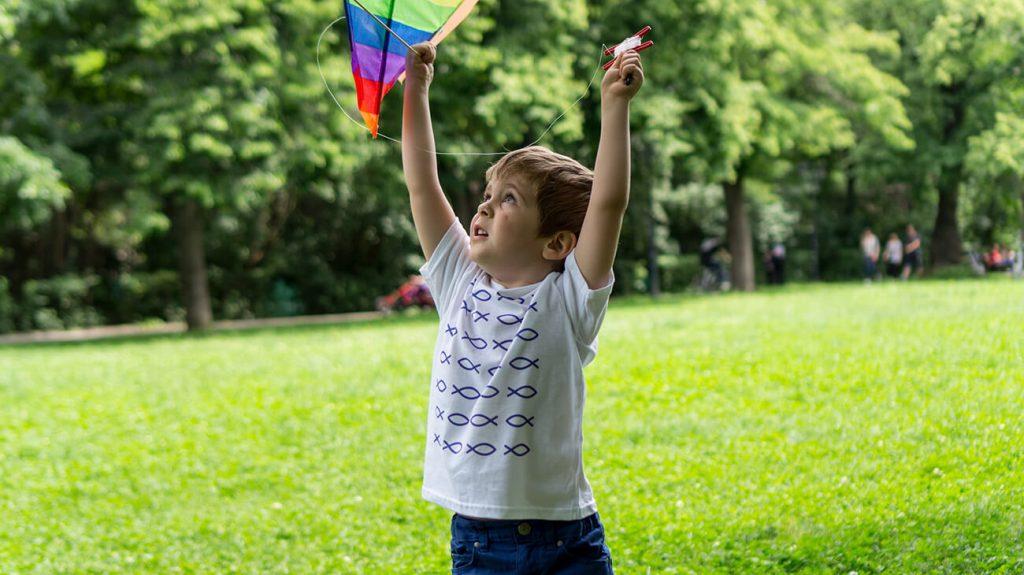 """Дете с хвърчило, което е облечено в бяла тениска от лятната колекция """"Обичаме морето"""""""