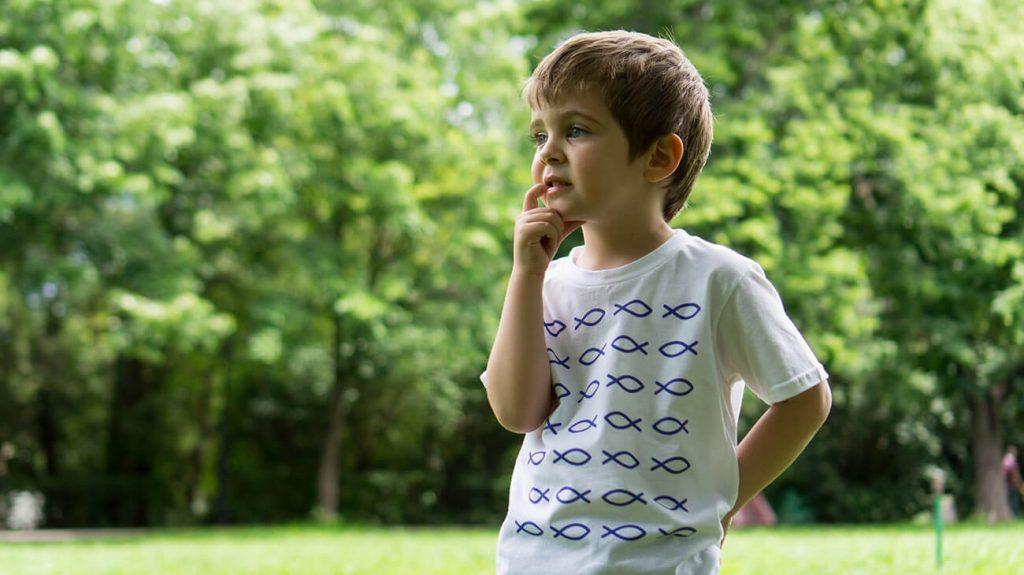 """Замислено дете, облечено в бяла тениска от лятната колекция """"Обичаме морето"""""""