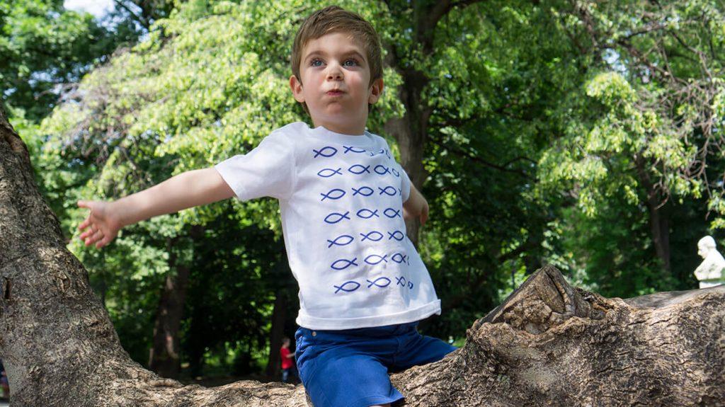"""Дете, което е седнало на дърво и е облечено в бяла теникса от лятната колекция """"Обичаме морето"""""""