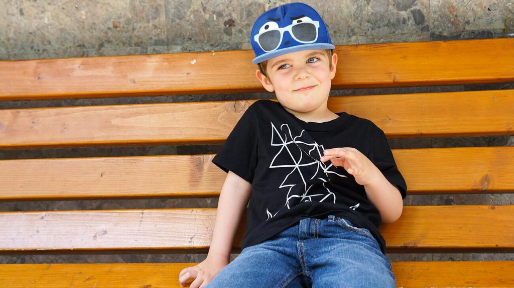Усмихнато дете на пейка облечено в черна тениска