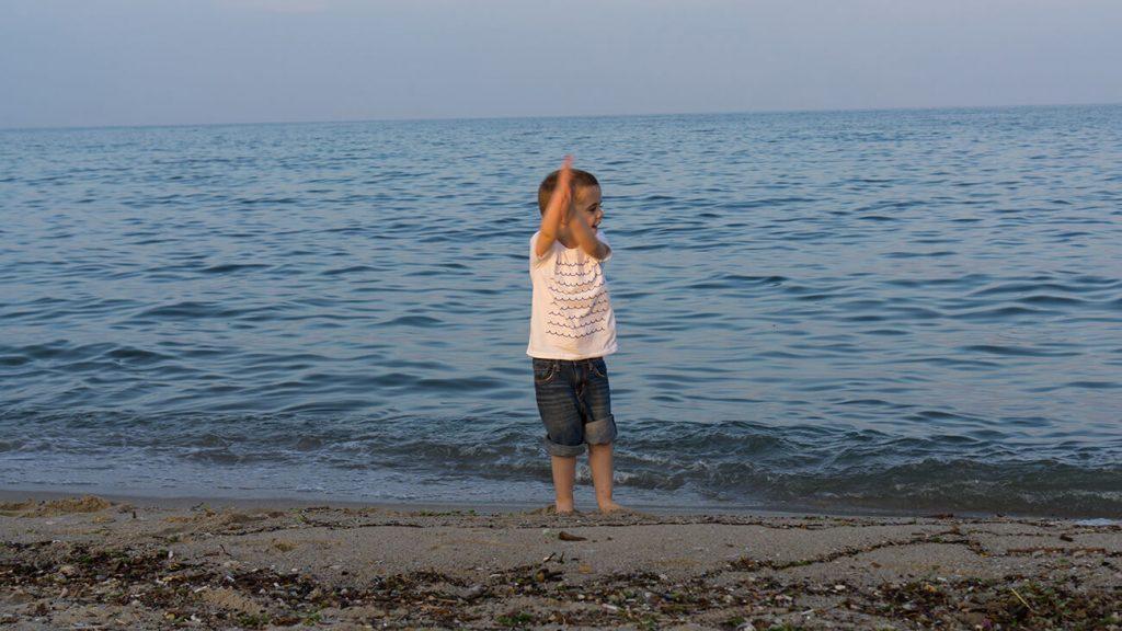 """Снимка на дете на плажа, което е облечено в бяла тениска от колекцията """"Обичаме Морето"""""""