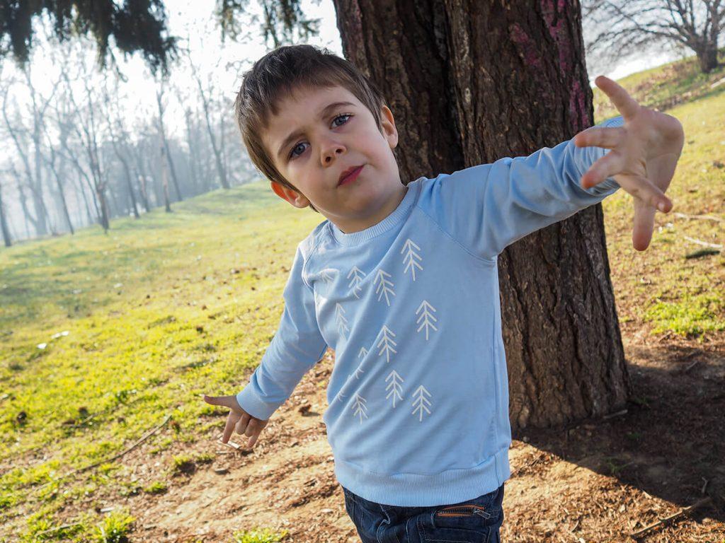 """Дете в парк, което е облечено в синя блузка от колекцията """"Цветна Зима"""""""