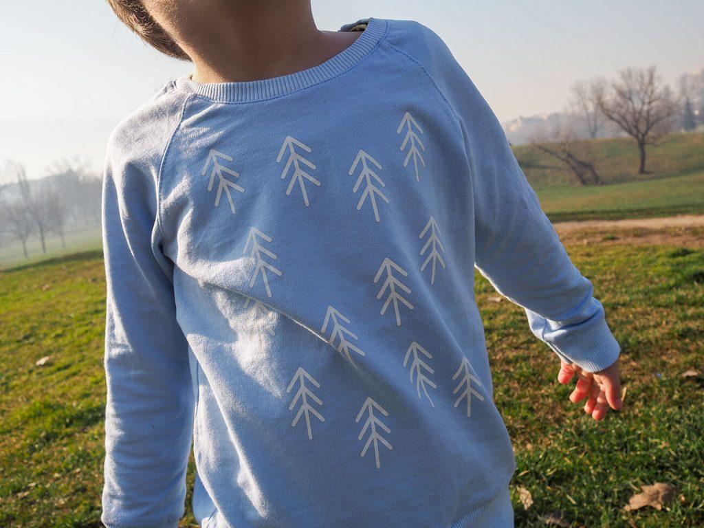 """Дете, което е облечено в синя блузка от колекцията """"Цветна Зима"""""""